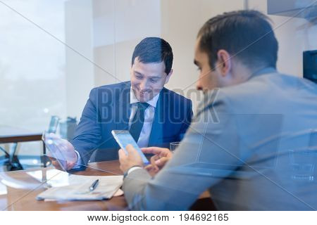 Image of two young businessmen using smart phones and touchpad at meeting in moder office.
