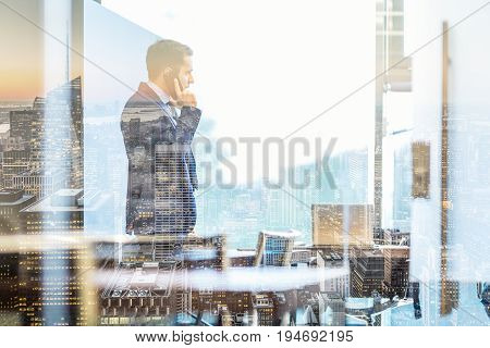 Businessman talking on a mobile phone while looking through modern corporate office window in New York city. Reflections of city skyscrapers in window glass.