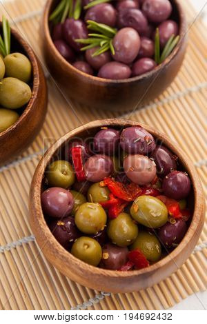 High angle view of various olives in wooden containers on place mat