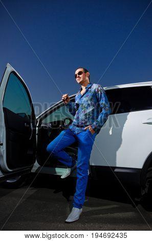 Man with cigar and gun near the car