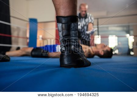 Low section of male boxer standing against referee by athlete lying in boxing ring