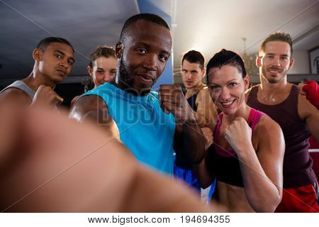 Portrait of young boxers standing in fighting stance at fitness studio