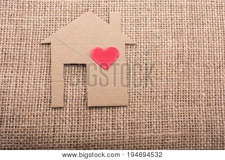 Heart shape on house shape cut out of paper with a canvas background