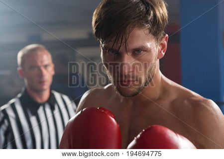 Referee looking at young male boxer in boxing ring at fitness studio