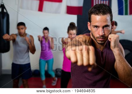Portrait of young male practicing boxing against flags in fitness studio