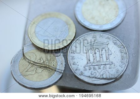 Frozen Assets: Greek euro and Drachme coins in ice