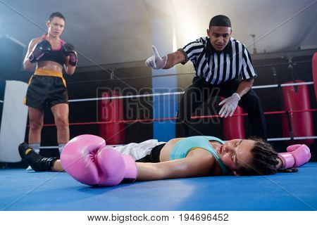Female boxer looking while referee counting by athlete in boxing ring