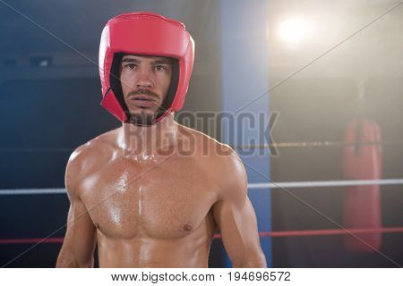 Portrait of shirtless male boxer wearing red headgear in boxing ring