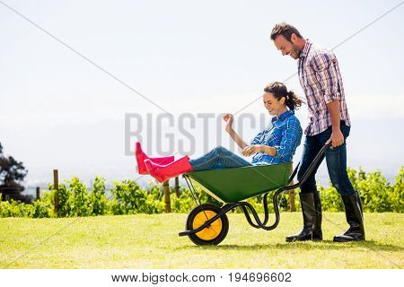 Young man pushing woman sitting in wheelbarrow at lawn on sunny day