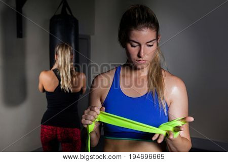 Beautiful woman tying hand wrap on hand in fitness studio