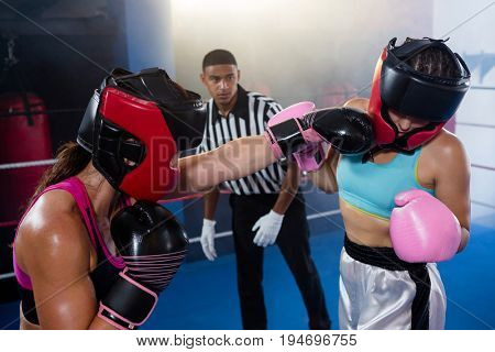Male referee looking at female boxer punching competitor in boxing ring