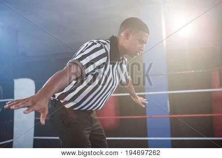 Young male referee showing hand sign in boxing ring at fitness studio