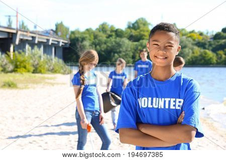 Young boy standing with crossed hands outdoor. Volunteer concept