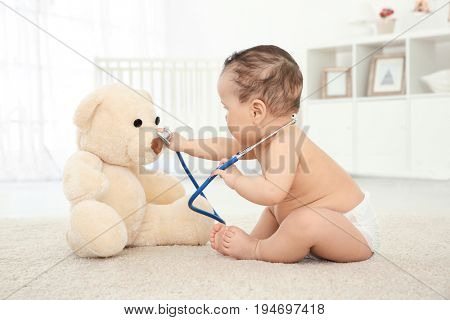 Cute little baby with stethoscope and toy bear playing at home