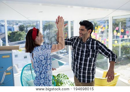 Happy couple giving high five to each other in the office
