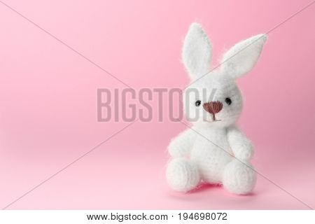 Cute handmade bunny toy on color background, closeup