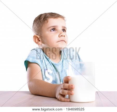 A dreamy little boy with golden hair in a blue t-shirt holds his big and transparent glass full of delicious healthful milk and looks away, isolated on a white background.