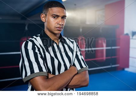 Portrait of confident male referee with arms crossed against boxing ring