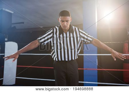 Male referee gesturing with arms outstretched in boxing ring