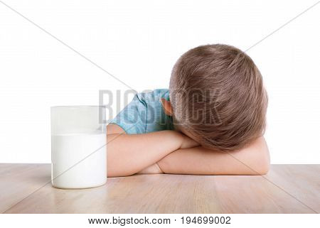A big spacious glass full of organic and tasty white milk and a sad charming blonde boy in a blue T-shirt. The Charming little boy is lying on his crossed hands on the classic table.