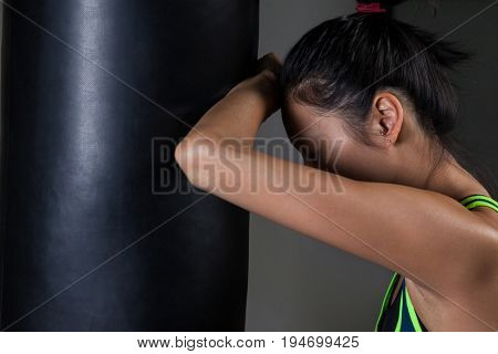 Exhausted female boxer leaning on punching bag in fitness studio