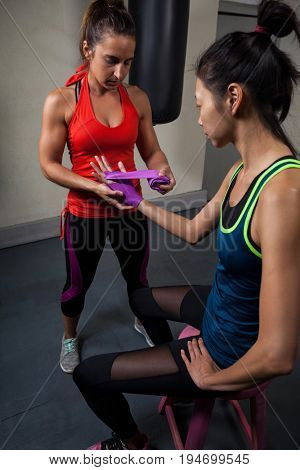 Trainer tying hand wrap on woman hand in fitness studio