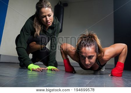Trainer assisting woman in exercise at fitness studio