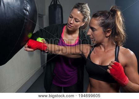 Trainer assisting woman in boxing at fitness studio