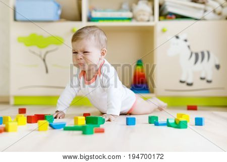 Cute sad crying baby playing with colorful wooden blocks toys. New born child, little girl looking at the camera and crawling. Family, new life, childhood, beginning concept. Baby learning grab