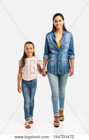 Mother and her little daughter walking together going to school