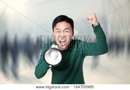 Young man with megaphone and blurred crowd on background. Workers strike concept