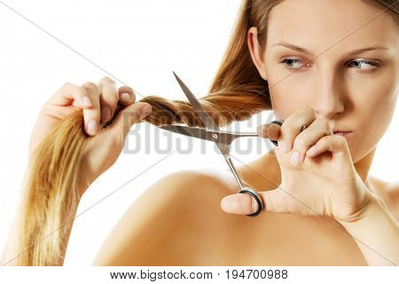 Attractive young woman is cutting her long natural hair