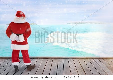 Santa Claus standing on deck and looking at seascape. Christmas and New Year vacation