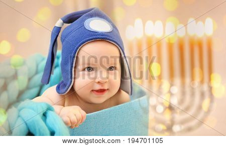 Little child in boxon blurred festive lights background. Baby's First Hanukkah