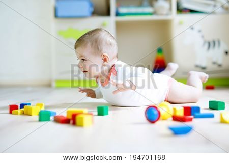 Cute happy smiling baby playing with colorful wooden blocks toys. New born child, little girl looking at the camera and crawling. Family, new life, childhood, beginning concept. Baby learning grab