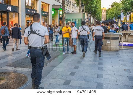 PARIS, FRANCE - JULY 2, 2017: policemen patrolling the Avenue des Champs Elysees from the Place Charles de Gaulle, Arc de Triomphe. Keeping security after recent terrorist attacks in Paris.