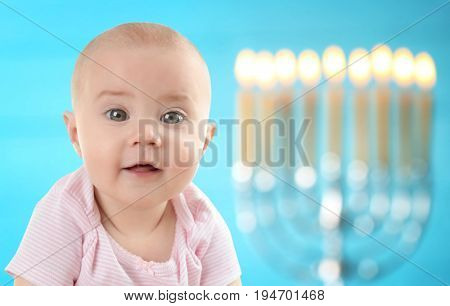 Little child on blurred festive lights background. Baby's First Hanukkah