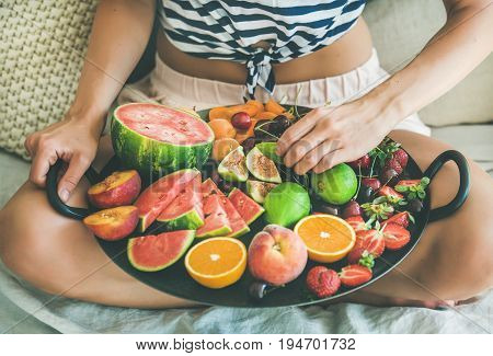 Summer healthy raw vegan clean eating breakfast in bed concept. Young girl wearing striped home shirt sitting and taking fruit from tray full of fresh seasonal fruit