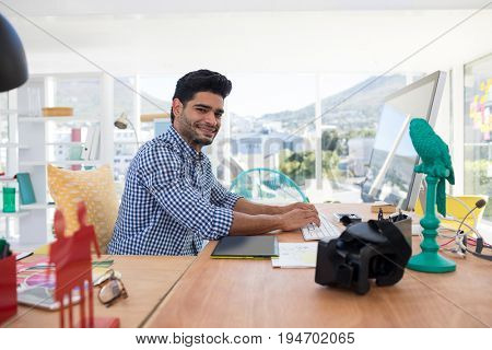 Graphic designer working on computer at desk in the office