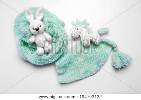 Handmade knitted toys with baby clothes isolated on white