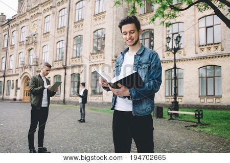 Handsome student reading an interesting book and standing in front of the camera outside with other students on the background