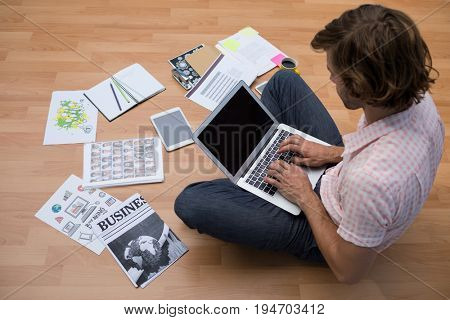 Male executive using laptop while sitting on floor in the office