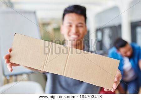 Asian student holding empty sign in creative workshop brainstorming exercise