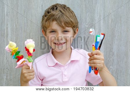 Happy little kid boy holding marshmallow skewer in one hand and toothbrushes in another. Child with different unhelthy colorful sweets. Healthy food and teeth concept.