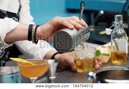 Bartender is pouring cocktail from shaker into the glass