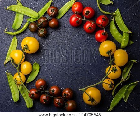 Food cooking background with red and yellow tomatoes and green pea. Copy space, top view, black background