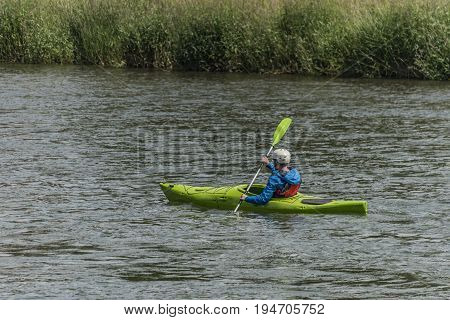 Green kayak on Dunajec river with passangers in summer day