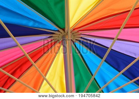 Close up of rainbow colored parasol umbrella for UV protection for summer outdoor recreation and sports spectators