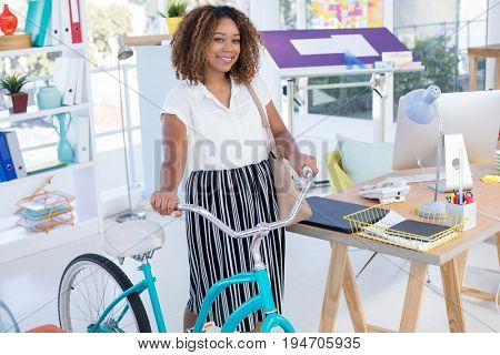 Portrait of female executive walking with bicycle in the office