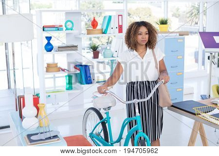 Female executive walking with bicycle in the office
